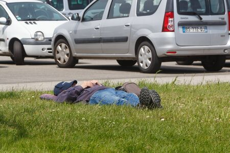 GUIPAVAS, FRANCE – JUNE 01 : man sleeping on grass near a parking during a sunny day, June 01, 2019