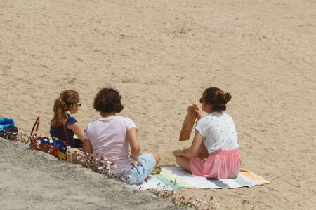 GUIPAVAS, FRANCE – JUNE 01 : family eating sandwiches at the beach, June 01, 2019
