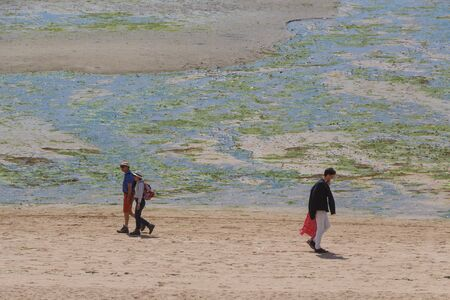 GUIPAVAS, FRANCE – JUNE 01, 2019 : Two couples walking on the beach at low tide