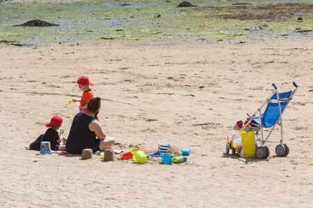 GUIPAVAS, FRANCE – JUNE 01 : family playing with sand and buckets at the beach, June 01, 2019
