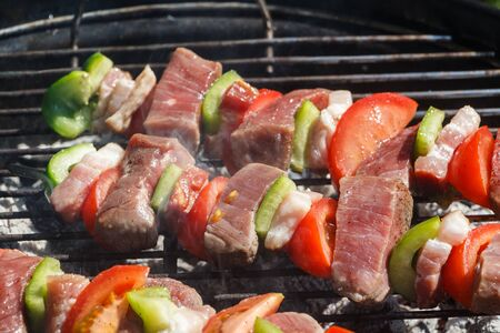 Beef brochettes grilling on the grid of a barbecue