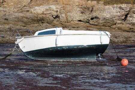 Boat grounded at mooring during low tide in Brittany Imagens