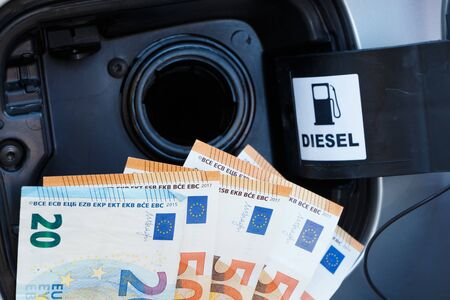 Money near a car tank to symbolize the cost of fuel Imagens