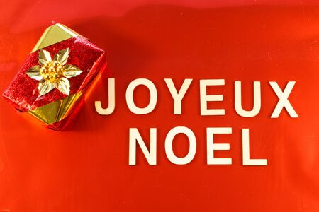 Merry Christmas in french language and gift on red background Imagens - 132682275