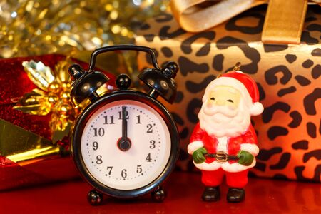 Santa Claus figurine, black alarm clock and gifts Imagens - 132265412