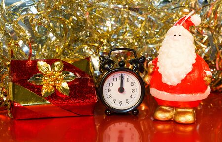 Santa Claus figurine, gift, alarm clock and golden tinsel Imagens - 132682305