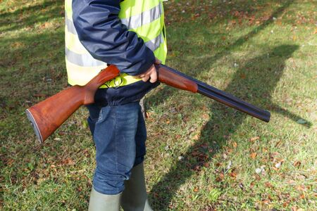 Hunter with its rifle in the woods during autumn