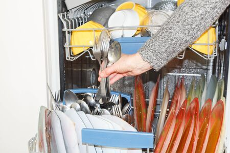 To put dirty crockery in the dishwasher in a kitchen Imagens - 132682349