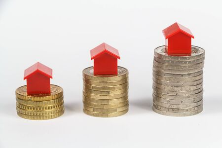 Euro coins and small plastic houses to symbolize the cost of houses Imagens - 132682352
