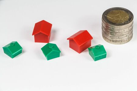 Euro coins and small plastic houses to symbolize the cost of houses Imagens - 132563129