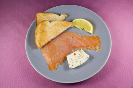 Plate of smoked salmon with fish and vegetable terrine, toast and a piece of lemon Imagens
