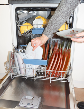 Hand of a woman who put crockery in the dishwasher Imagens - 132887652