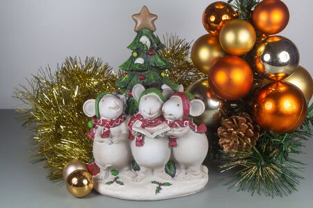 Mouses figurines singing, golden tinsel and baubles as decoration for Christmas