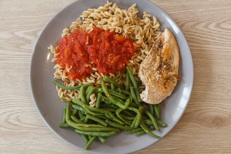 Light meal, pasta with tomato sauce, green bean and grilled chicken fillet Imagens - 132690072