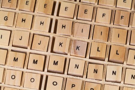 Alphabet letters written on wooden cubes in a box