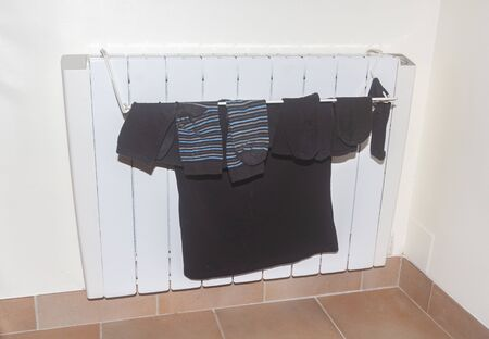 Clothes drying on the radiator in an house Imagens - 133116556