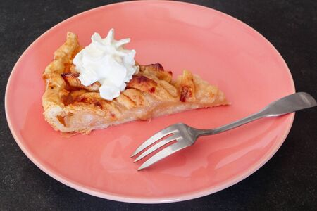 Piece of apple tart with whipped cream and a fork on a plate