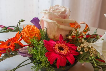 Flowers arrangement with rose and lily in a plastic bowl Imagens - 133277863