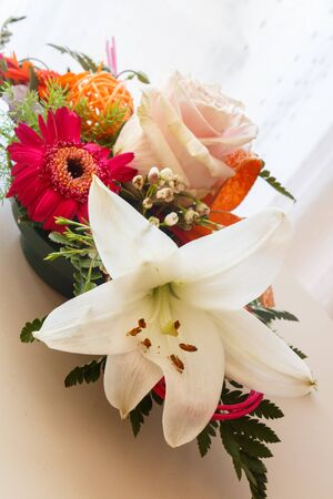 Flowers arrangement with rose and lily in a plastic bowl
