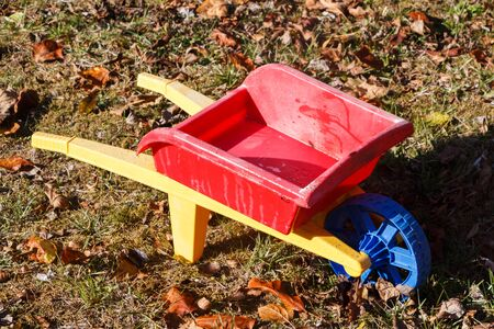 Outdoor toy, red and yellow wheelbarrow in plastic