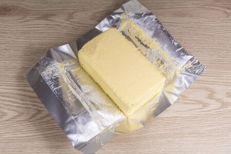 Pack of salted butter unwrapped on wooden background