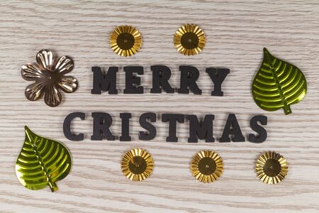 Merry christmas and metallic decorations in the shape of flower and leaves