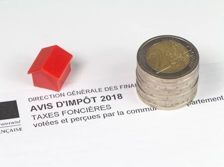 Property tax written in french language, small house and heap of two euros coins