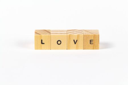 Love written with wooden cubes on white background Imagens