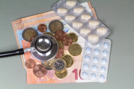 Black stethoscope, pack of pills, euro coins and banknotes as concept for the cost of health Imagens