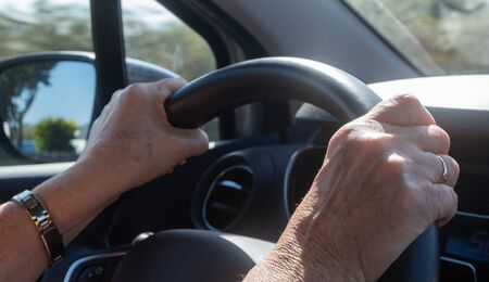 Hands of a woman on a steering wheel