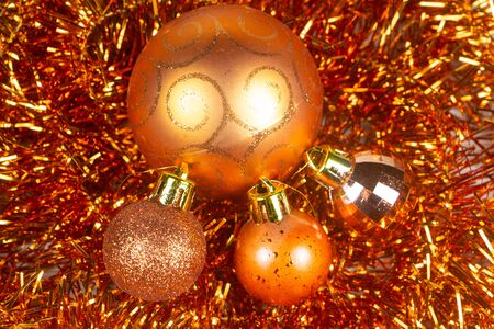 Baubles on orange tinsel as decoration for Christmas Stock Photo