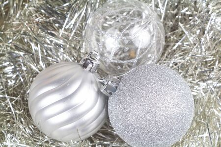 Baubles on silvery tinsel as decoration for Christmas Stock Photo