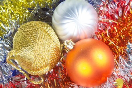 Three baubles on tinsels as decoration for Christmas