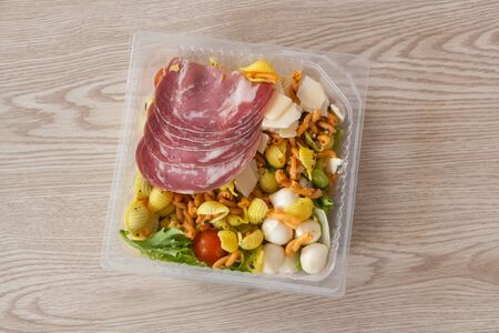 Industrial mixed salad with coppa and italian cheeses in a plastic bowl