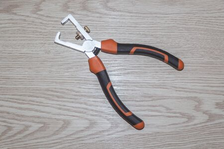 Professional electrician wire stripper on wooden background