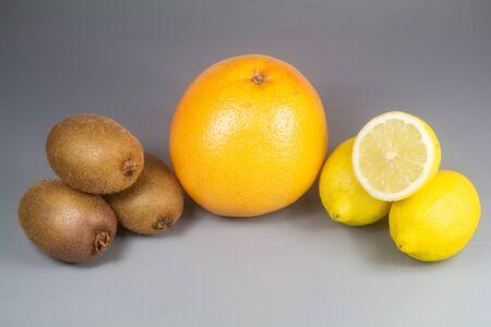 Winter fruits, grapefruit, kiwis and lemons on wooden background