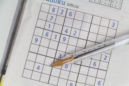 Sudoku game in a newspaper and pen Imagens