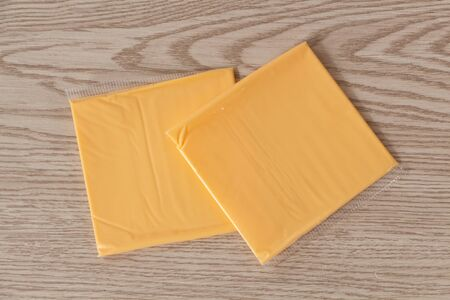Two portions of processed cheese with cheddar in plastic packaging Imagens