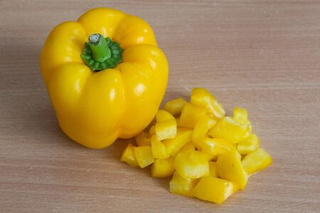 Whole and pieces of yellow pepper on a table