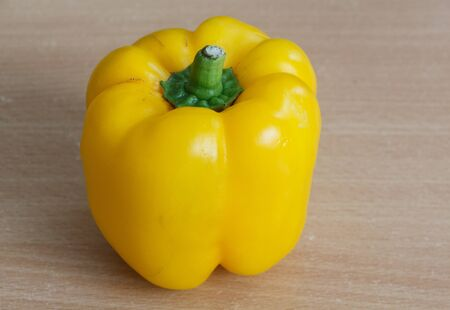 One whole yellow pepper on a wooden table