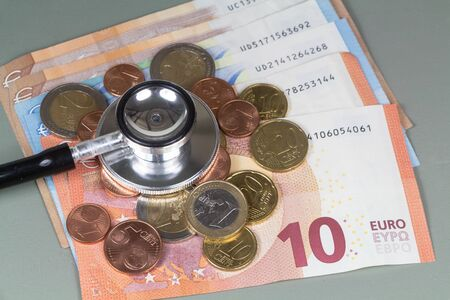 Black stethoscope, euro coins and banknotes as concept for the cost of healthcare Imagens
