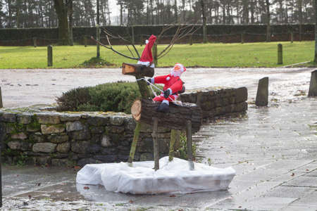 Santa Claus on a reindeer made in wood logs as decoration in a street Standard-Bild