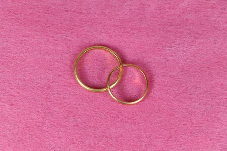 Two wedding rings in gold on pink background