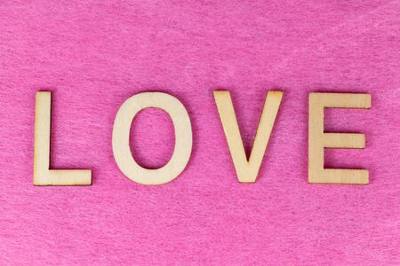 Love in wooden letters on pink background 版權商用圖片 - 139497086