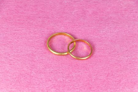 Two wedding rings made in gold on pink background