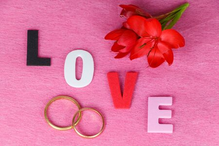 Two wedding rings, red flowers and love written in colored letters for Valentines Day 版權商用圖片