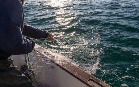 Fisherman bringing back net in a boat in Brittany