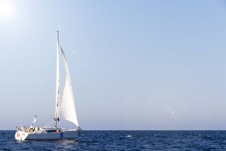 Sailboat with white sails under the sun in Brittany