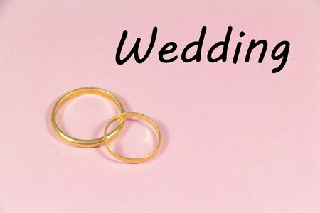Two wedding rings and wedding on pink background