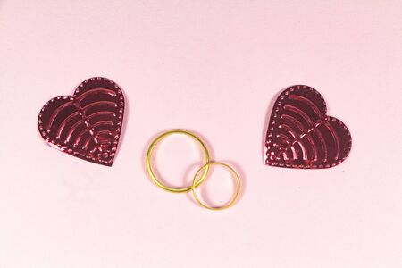 Two wedding rings and two pink hearts on pink background